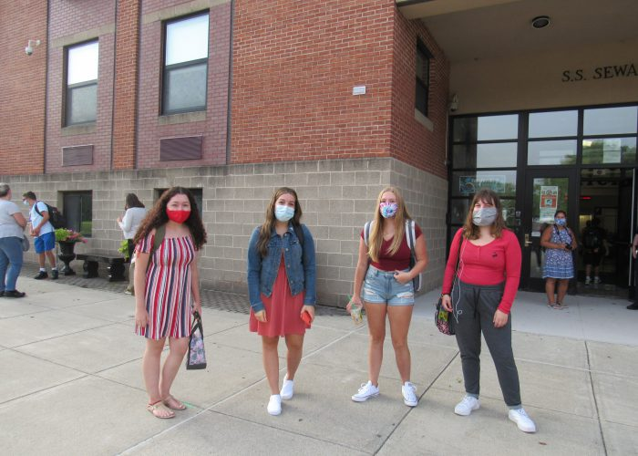 Sour young women all wearing masks stand in front of a brick building