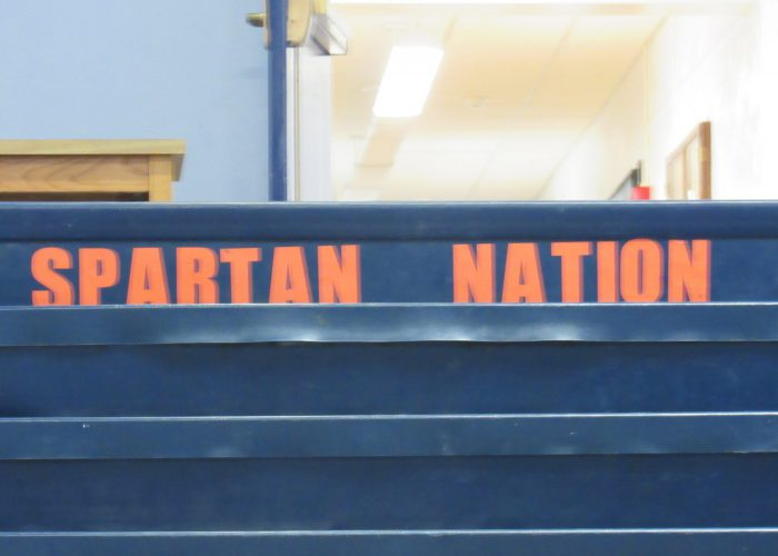 The words Spartan Nation in orange on a blue background