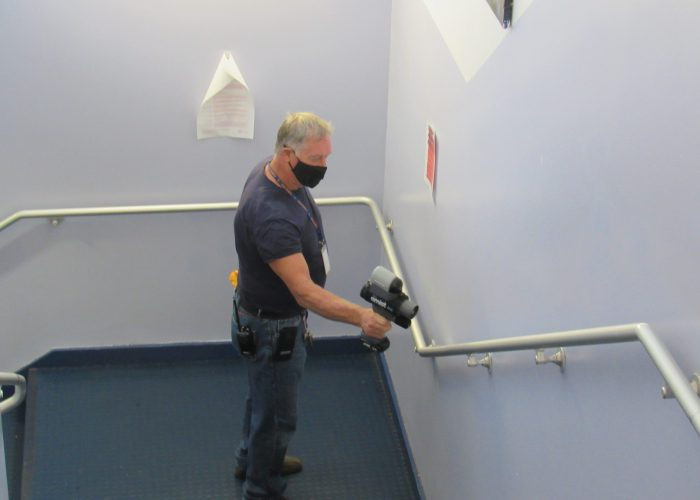 A man with blonde hair wearing a black mask uses a hand-held device to sanitize a handrail in a hallway.