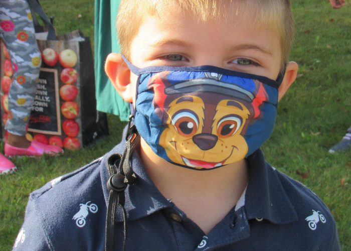 A young boy with blonde hair and blue eyes wearing a blue shirt and a mask with a picture of a cartoon chipmunk on it.