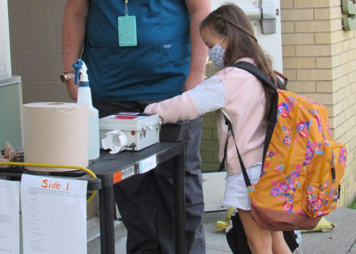 A young elementary girl with a large backpack puts her wrist into a device that takes her temperature