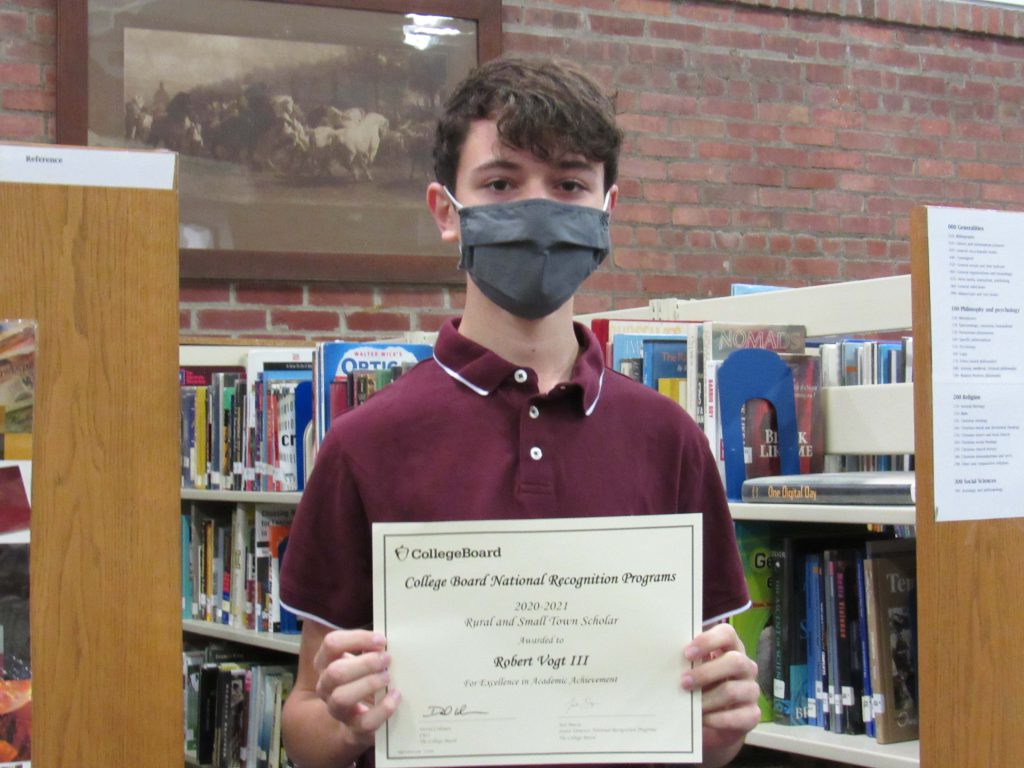 A young man in a maroon shirt wearing a black mask holds a certificate