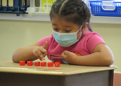 A little girl with dark hair in braids wearing a blue mask and a pink shirt sits at her desk counting pink items.