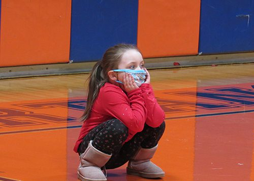 A kindergarten girl with a long ponytail wearing a blue mask, red shirt and gray boots squats during gym class.