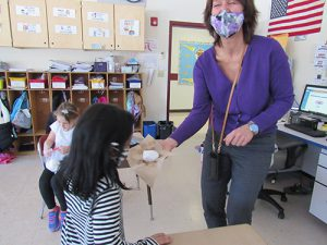 A woman holds a snowball in her hand on a piece of brown paper towel showing it to a kindergarten student. The woman is laughing behidn her mask.