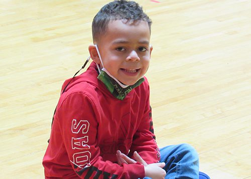 A boy with short hair smiles with his mask down around his chin. He is wearing a red sweatshirt and sitting on the gym floor.