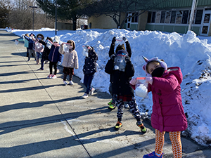 A line of kindergarten students outside with a snow bank behind them. All are wearing masks and separated from each other.