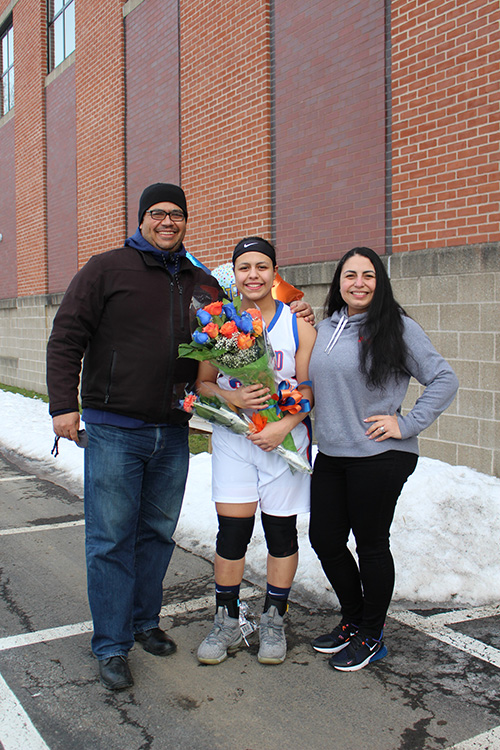 Three people standing outside, with a brick building behind them. From left, a man smiling, wearing a black jacket and hat, a young woman in the center dressed in a white basketball uniform holding flowers, and a young woman at right, wearing a gray sweatshirt and long dark hair. All are smiling.