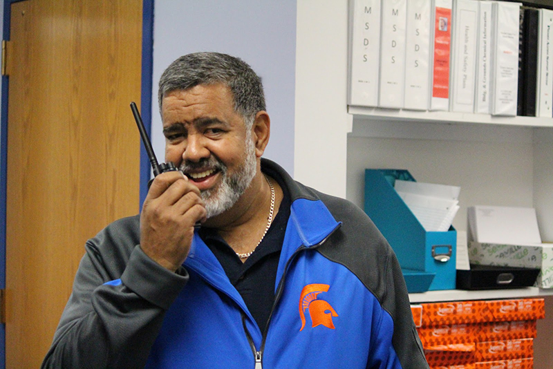 A man with salt and pepper hair and beard smiling. He is holding a walkie-talkie up to his mouth. He is wearing a blue jacket with an orange spartan logo on the front right chest.