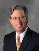 A man with short brown hair, wearing glasses, a black suit, white shirt and tan tie. He is smiling.