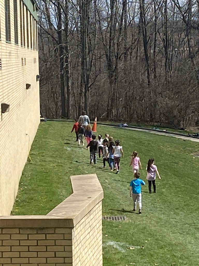 A photo from above where a line of students are walking in the grass with a building on the left.