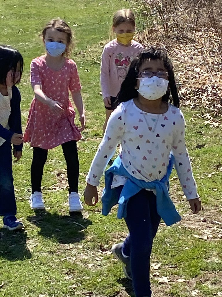 A girl with dark hair and a mask walks in front as three others walk behind.