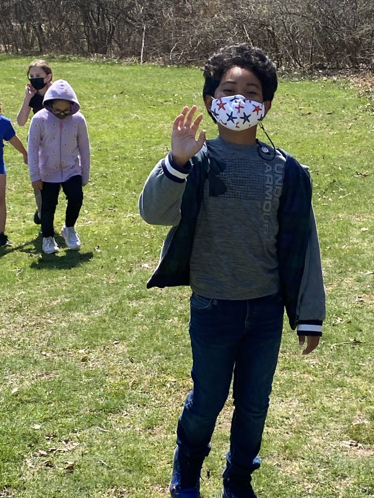An elementary student wearing a printed mask waves as she walks.