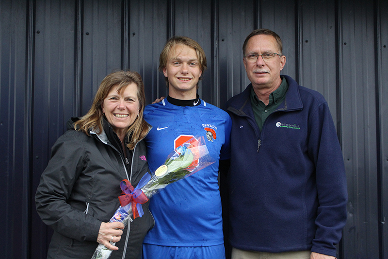 A high school senior boy wearing a blue soccer jersey with an orange number 3 has an arm around a woman smiling holding flowers and a man wearing a blue jacket.