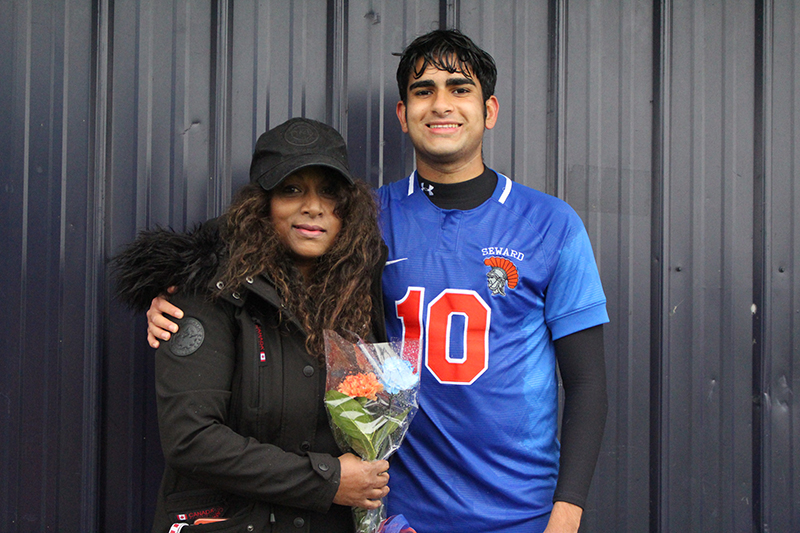 A high school senior boy wearing a blue soccer jersey with number 10 in orange smiles and has his arm around a woman wearing a winter jacket and hat, holding flowers.
