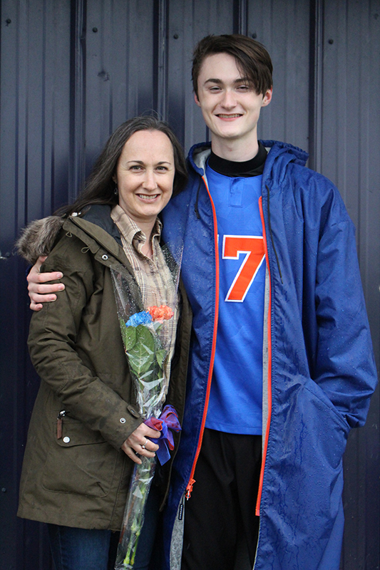 A high school senior boy wearing a blue soccer jersey with an orange number 7 on it smiles. He has dark hair and is wearing a  blue winter jacket. He has his arm around a woman with long brown hair, wearing a green winter jacket. They are smiling.