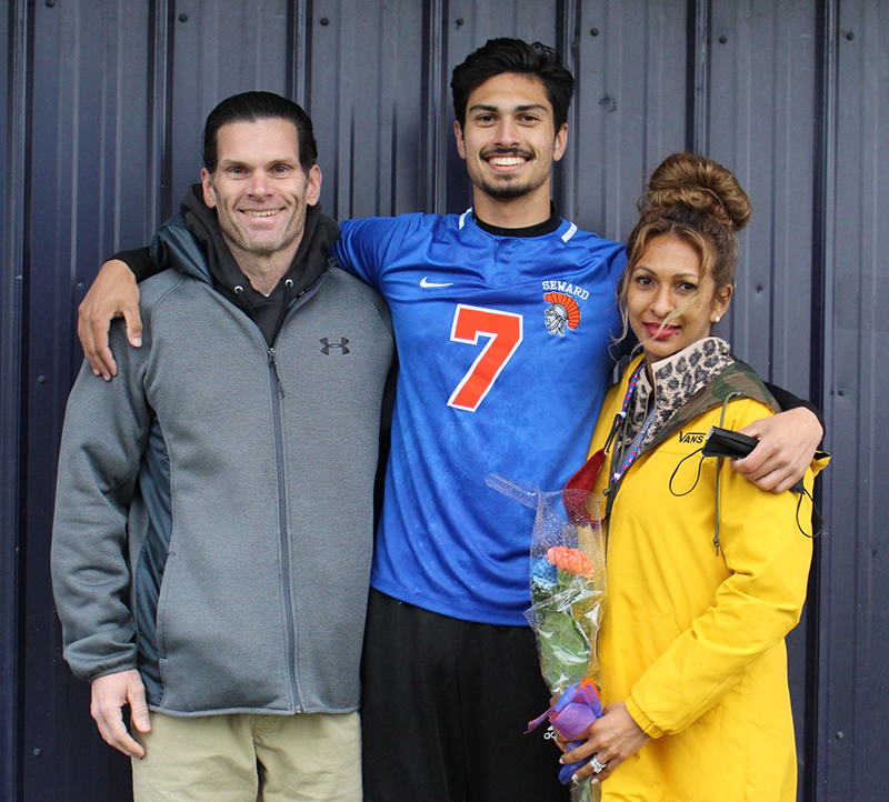 A high school senior boy wearing a blue soccer jersey and the number 7 in orange smiles broadley. He has dark hair and has an arm around a man with dark hair and green jacket and a woman with brown hair piled on top of her head, wearing a yellow jacket holding flowers.