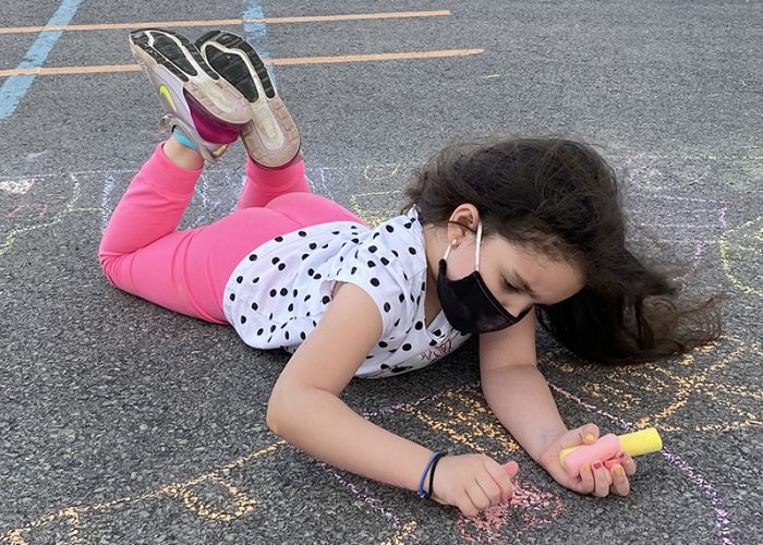 Little girl with long dark hair, pink pants and a short-sleeve printed shirt lies on the blacktop and draws with big pieces of colored chalk.
