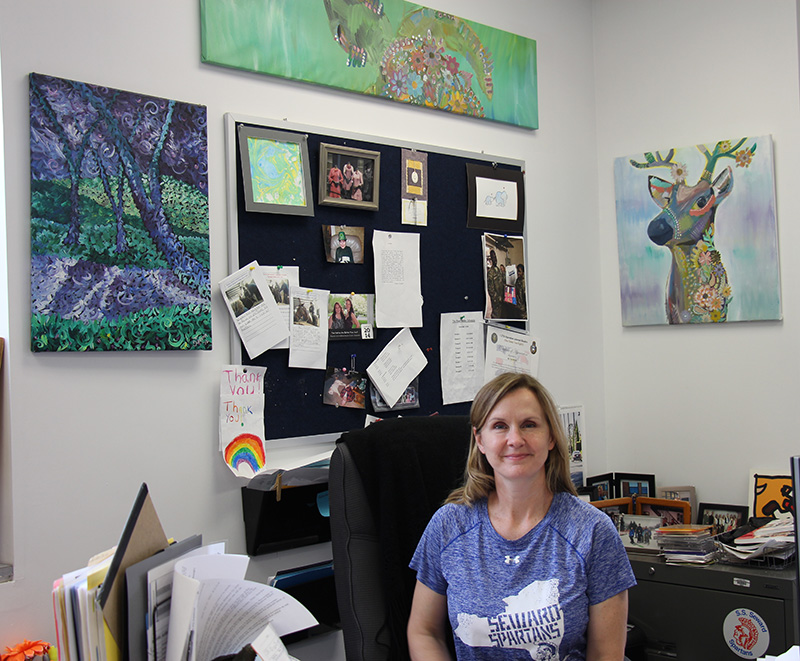 A woman with shoulder-length blonde hair sits at a desk smiling. She is wearing a light purple shirt with the state of New York on it . Inside the graphic  it says Seward Spartans. Surrounding her on th ewalls is all artwork done by students.
