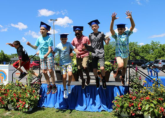 A group of six fifth-grade boys jump off the platform where they received their moving-up certificates. They are all wearing graduation caps. The sky is blue behind them.