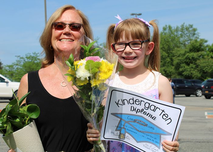 A little girl with blonde hair and glasses holds flowers and a kindergarten diploma. she is standing next to a teacher with blonde hair, sunglasses wearing a black dress and holding a plant.
