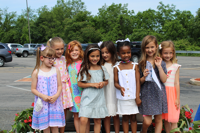 Eight kindergarten girls stand together, smiling. They are all wearing sun dresses and smiling. In the background are trees and blue sky.