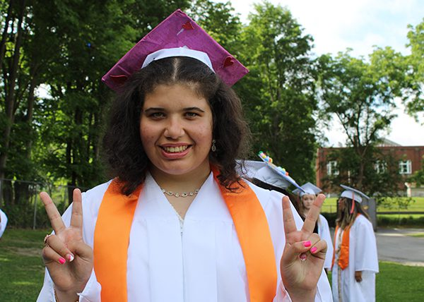 A young woman in white cap and gown and gold drape smiles and holds up peace signs.