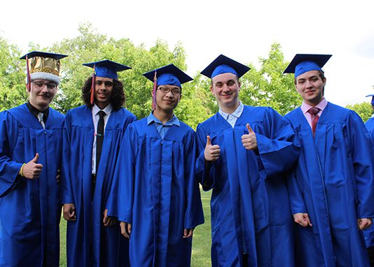 A group of five high school senior boys all wearing blue caps and gowns. One has a gold crown under his cap.