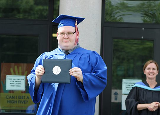 A young man wearing a blue cap and gown holds his diploma. A woman on the right smiles.