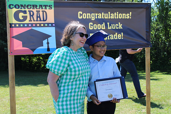 A teacher wearing a green check dress stands with a young male student who is holding his certificate. He has on a blue button-down shirt, glasses  and a blue graduation cap. They are in front of a sign that says Congratulations! Good Luck 5th Grade!