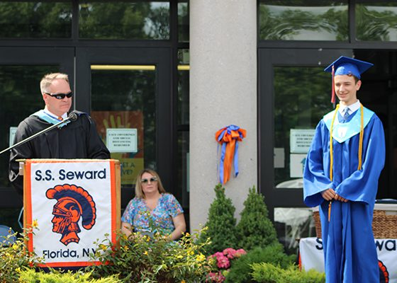 A high school boy graduating with blue cap and gown and gold threads around his neck on the right, a man in black gown sunglasses talking at the podium. There is a sign that says S.S. Seward Florida NY