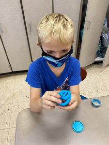 A boy with blonde hair, wearing a blue shirt and mask, holds up a round of blue play-doh in a smiley face shape.