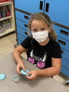 A girl with light, long hair wearing a black t shirt and white mask, holds a flattened round of blue play-doh.