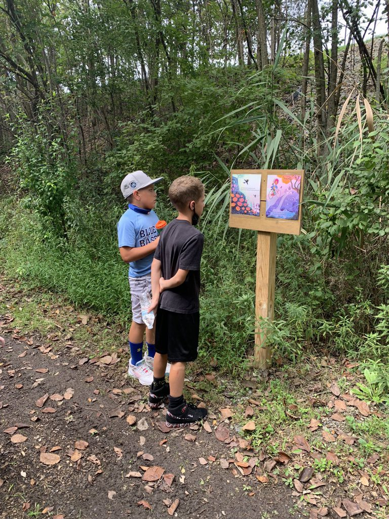 Two elementary age boys stand on a path with trees around them looking at a book open on a wooden post.