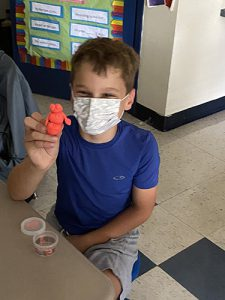 An elementary age boy with brown hair wearing a blue tshirt wearing a white mask holds up an orange man made of play-doh