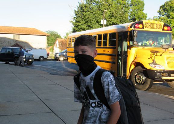 A boy wearing a black and white short-sleeve shirt, carrying a backpack andwearing a black facemask walks from a bus into a building. There is a bus in the background.