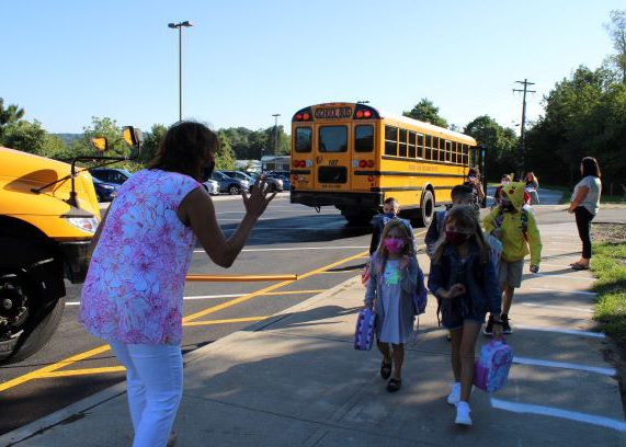 A woman in white pants and pink and white shirt waves to children as they are walking toward her after getting off school buses, which are in the background. All are wearing masks.