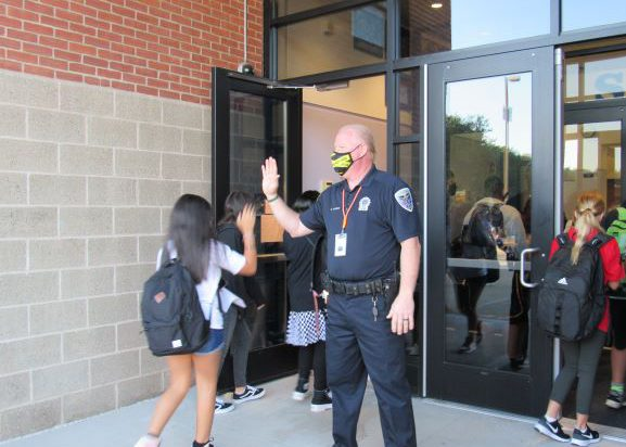 A police officer high fives a young woman as she enters a school building.