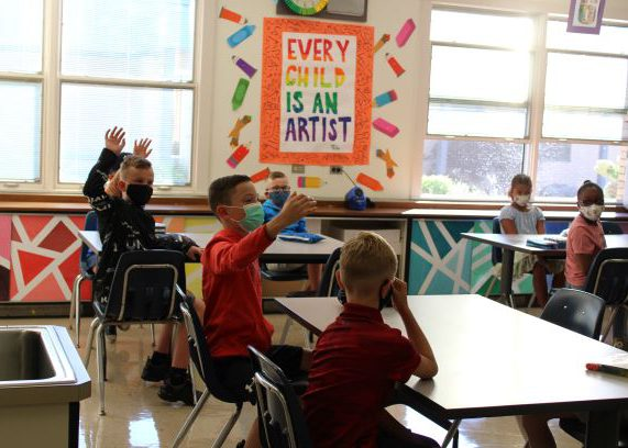 A brightly colored poster on the wall says Every Child is an Artist. The older elementary students sit at tables in the class and three are raising their hands. Others are looking on. All have masks on.