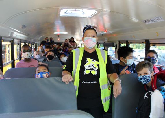 A woman in a black shirt with bright orange vest stands in the aisle of a bus. Her students are all around standing and peeking over the seats. All are wearing masks.