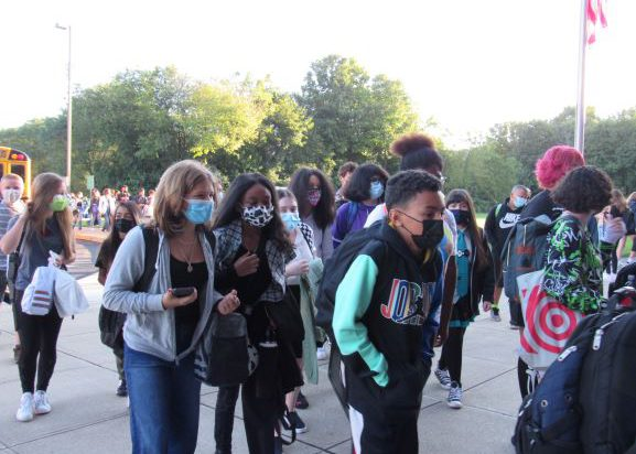 A large group of middle school students walk in the same direction. There is a bus in the background and a flagpole with the American flag. All kids have masks on.