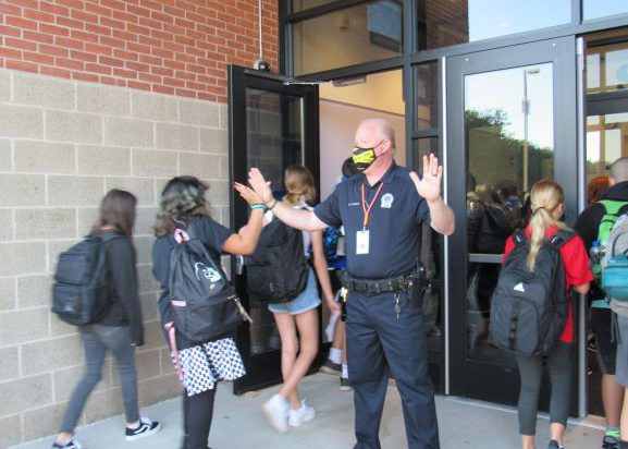 A police officer stands outside of a school building as two lines of students go past him. a young woman on the left side high fives him.