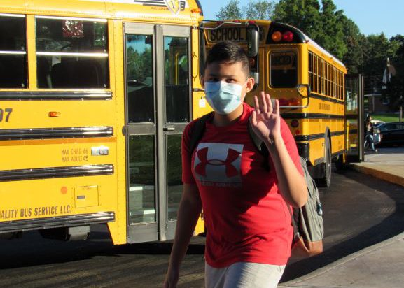 A middle school boy waves. He is wearing a red t shirt and a light blue mask.