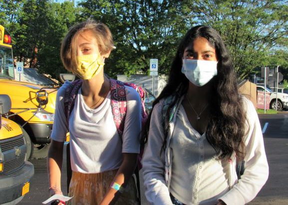 Two young women walk together with buses on the left. One has short blonde hair and is wearing a yellow mask, white shirt and printed pants. She is carrying a pink patterned backpack. The girl on the right has long dark hair and is wearing a light blue mask and a white long-sleeve shirt.