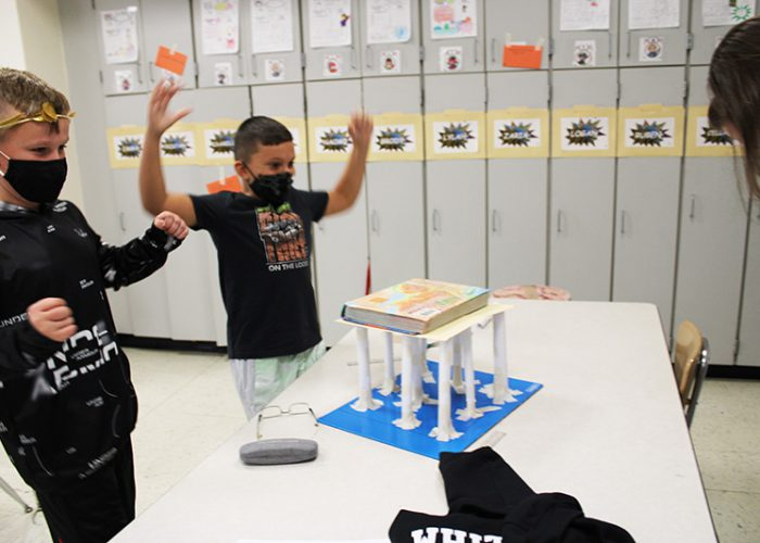 Two boys dressed in black shirts, wearing black masks hold their arms up joyfully as their project is successful. In front of them is ten columns made from white paper taped to a base. On top is a textbook.