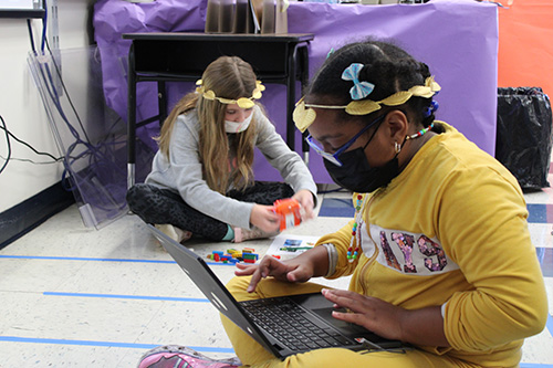 Two elementary age girls sit on the floor. Both are wearing gold leaf wreaths in their hair. One girl closest is wearing a yellow sweatsuit. She has classes and has a chromebook on her lap, that she is working on. The girl in the back has long hair and is using Legos to build a robot.