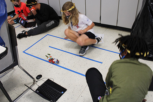 A student with long blonde hair watches as a small robot moves along the floor. Another student wearing a green shirt is watching.