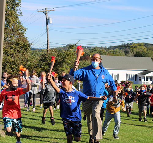 A group of elementary students and a teacher run holding torches made of cardboard tubes and orange paper.